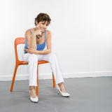 Smiling woman portrait. Portrait of pretty Caucasian woman sitting in modern chair Royalty Free Stock Photography