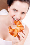 Smiling woman eating a croissant Stock Images