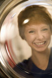 Smiling woman portrait through glass. Woman looking through the glass door of a front  loading washing machine Stock Photos