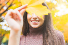 Smiling woman portrait with a yellow leaf in autumn Royalty Free Stock Photo