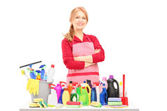 Smiling woman posing with cleaning supplies on a table Royalty Free Stock Image