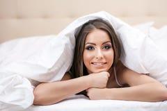 Smiling woman posing under blanket Royalty Free Stock Image