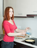 Smiling woman pouring dough  in frying pan Royalty Free Stock Photography