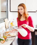 Smiling woman pouring milk in bowl Royalty Free Stock Photo