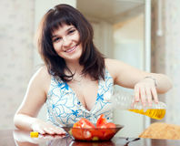 Smiling woman pouring oil to vegetables. Salad Stock Photo
