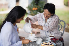 Smiling woman pouring tea in cup for daughter Royalty Free Stock Images