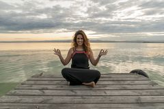 Smiling woman practicing meditation in the lotus yoga position on a wooden jetty stock images