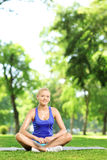 Smiling woman practicing yoga in a park Royalty Free Stock Photo