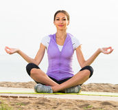 Smiling woman practise yoga cross-legged Stock Images