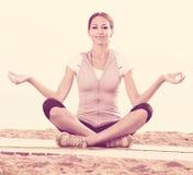 Smiling woman practise yoga cross-legged Royalty Free Stock Image