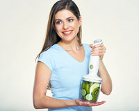 Smiling woman prepairing green smoothy in blender. Stock Photography
