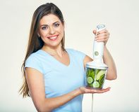 Smiling woman prepairing green smoothy in blender. Isolated studio portrait Stock Photo