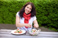 Smiling Woman Preparing a Bowl of Salad Royalty Free Stock Image
