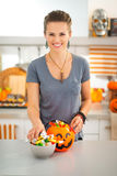 Smiling woman preparing halloween trick or treat candy for kids Stock Photos