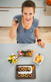 Smiling woman preparing horribly halloween treats for party. Kids will be stunned! Smiling woman in kitchen with spider toy in hand preparing horribly tasty Royalty Free Stock Images
