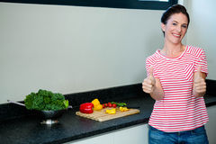 smiling woman preparing vegetables for dinner and giving a thumbs up Royalty Free Stock Photos