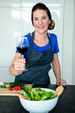 smiling woman preparing vegetables and drinking red wine Royalty Free Stock Photo