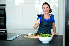 smiling woman preparing vegetables and drinking red wine Stock Photos
