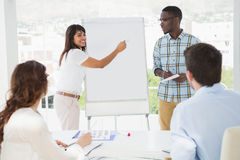 Smiling woman presenting and writing on whiteboard Royalty Free Stock Photo