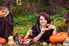 Smiling woman with pretzel near the vegetables in the autumn par Royalty Free Stock Photos