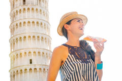 Smiling woman in profile with slice of pizza by Tower of Pisa Stock Image