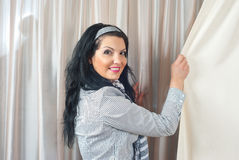 Smiling woman pulling drapery. Smiling woman standing at window with curtains and pulling drapes Stock Photos