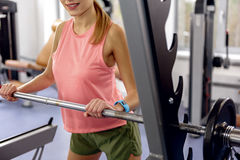 Smiling woman pumping iron in fitness center Royalty Free Stock Photo