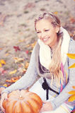 Smiling woman with pumpkin. Young smiling woman's sitting with the pumpkin in the field Stock Photography