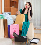 Smiling woman with purchases  speaking by mobile. At home Stock Photography