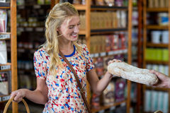 Smiling woman purchasing a loaf of bread Royalty Free Stock Photos