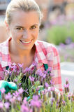 Smiling woman with purple flower garden center Stock Image