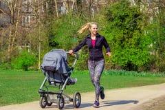 Smiling woman pushing baby buggy Royalty Free Stock Photos