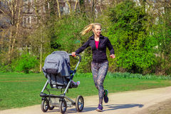 Smiling woman pushing baby buggy. Smiling young woman pushing baby buggy while exercising in a park Royalty Free Stock Photos