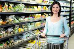 Smiling woman pushing trolley in aisle Royalty Free Stock Photo