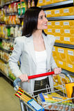 Smiling woman pushing trolley in aisle Royalty Free Stock Photography
