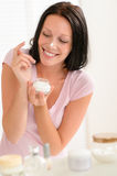 Smiling woman put moisturizer cream on nose Royalty Free Stock Photos