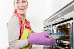 Woman putting cake into oven of kitchen Stock Photos