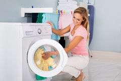 Smiling Woman Putting Clothes In Washing Machine. Young Smiling Woman Loading Untidy Clothes In Washing Machine In Utility Room Stock Photos