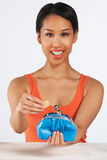 Smiling Woman Putting Coin In Purse Stock Photo