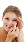 Smiling woman putting a contact lens Royalty Free Stock Photos
