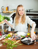 Smiling woman putting  fish in flour into  pan Stock Photos
