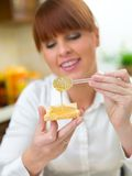 Smiling Woman Putting Honey on Bread Royalty Free Stock Photography