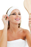 Smiling woman putting mascara Royalty Free Stock Images