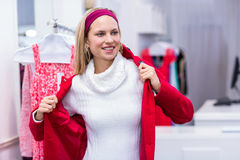 Smiling woman putting on red coat Stock Image