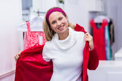 Smiling woman putting on red coat Royalty Free Stock Photo