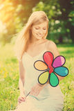 Smiling woman with a rainbow flower outdoors Royalty Free Stock Photo