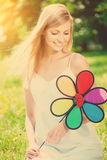 Smiling woman with a rainbow flower outdoors Stock Image
