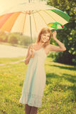 Smiling woman with a rainbow umbrella outdoors Stock Photos