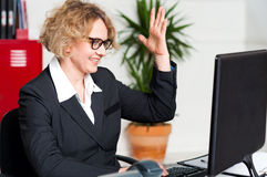 Smiling woman with raised arm looking at screen Royalty Free Stock Images