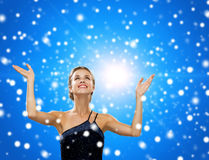 Smiling woman raising hands and looking up Royalty Free Stock Image